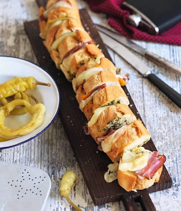 Gespicktes Baguette mit Kräuterbutter, Speck, Pfefferoni und Bergkäse